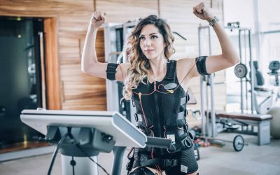 EMS electro stimulation women exercises with coach in modern gym. Electric muscle stimulation workout